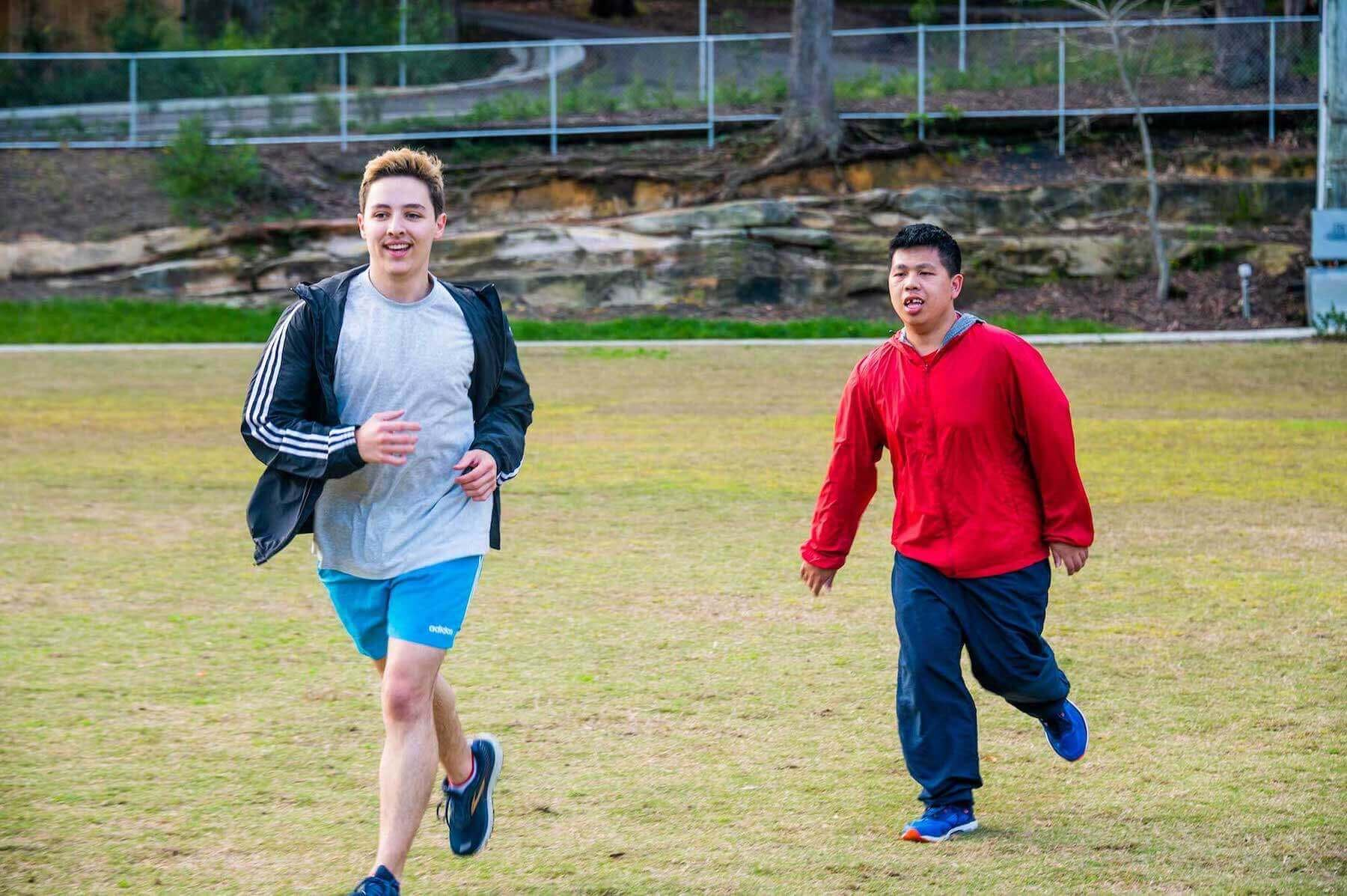 Two men running on grass in exercise clothes.