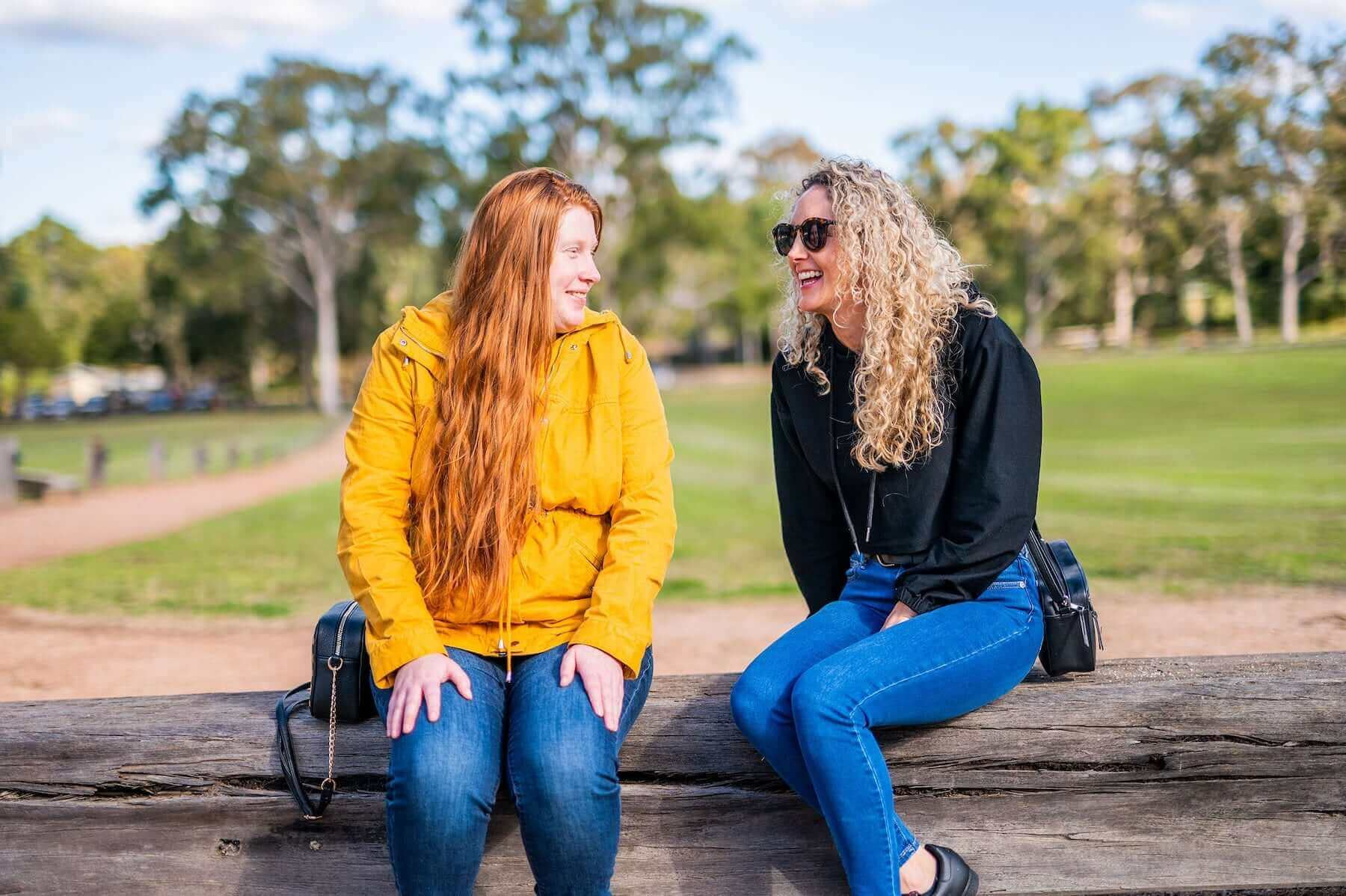 Two women laughing and talking whilst sitting in a park and looking at each other.