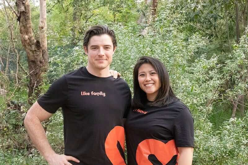 Mat and Jenna in their Like Family shirts with trees behind them