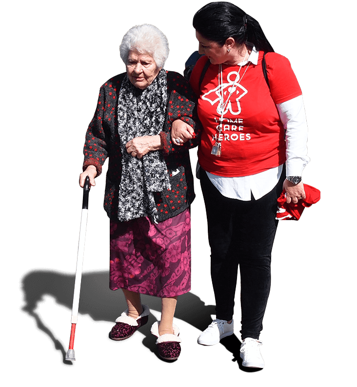 A female Social Carer holding the arm of an elderly woman, helping her to walk while turning to face her while saying something. The elderly woman has a walking stick.