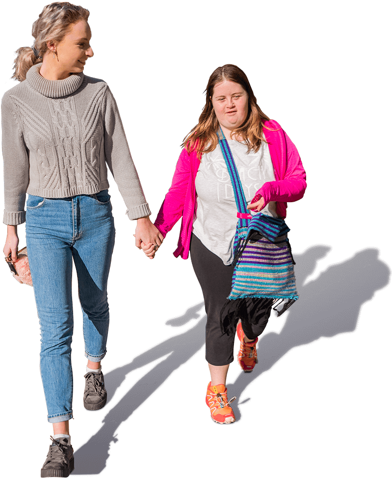 Two young women, one a social carer and one with a disability, walking together holding hands.